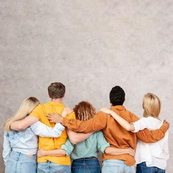 Vista posterior amigos abrazándose y mirando hacia arriba