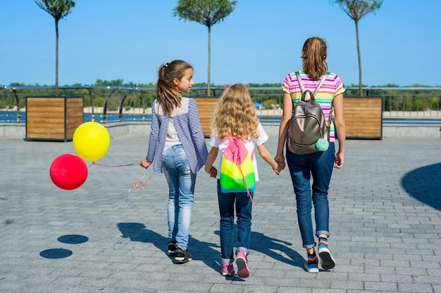 Vista posterior de amigos caminando juntos en una ciudad