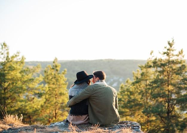 Vista posterior amigos sentados en la naturaleza