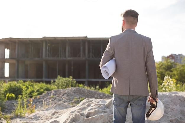 Vista posterior de la arquitectura masculina que sostiene el modelo y el casco que mira el emplazamiento de la obra