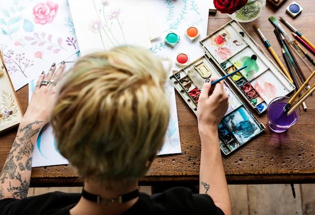 Vista posterior del artista mujer trabajando pintura flores color del agua en papeles