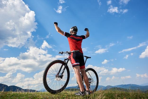 Vista posterior del atleta ciclista deportista profesional de pie con la bicicleta en la cima de la colina, rasing las manos, contra el cielo azul con nubes en un día soleado de verano