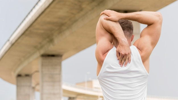 Vista posterior atlético hombre estirando