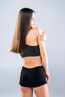 Vista posterior de la atractiva joven en ropa deportiva posando en gris. modelo femenino delgado y saludable en estudio.