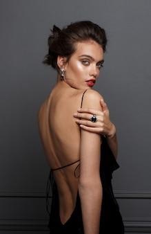 Vista posterior de una atractiva modelo femenina en vestido negro con hombros descubiertos, lleva aretes y anillos de piedra azul sobre fondo gris oscuro.
