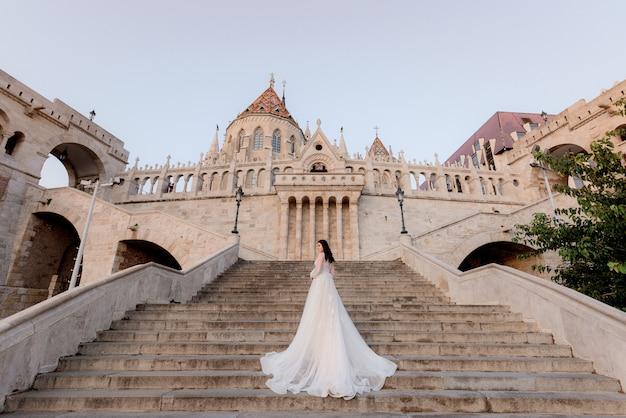 Vista posterior de una atractiva novia en las escaleras de un edificio histórico en la hermosa y cálida noche de verano