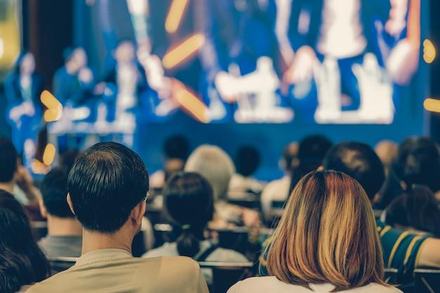 Vista posterior de la audiencia escucha a los oradores en el escenario en la sala de conferencias o en la reunión del seminario