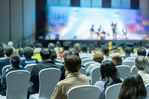 Vista posterior de la audiencia escucha a los oradores en el escenario de la sala de conferencias o la reunión del seminario