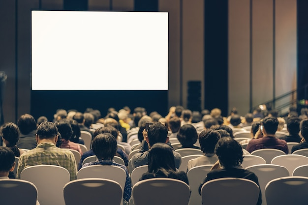 Vista posterior de la audiencia escuchando a los oradores en el escenario de la sala de conferencias