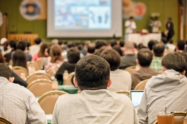 Vista posterior de la audiencia escuchando a los oradores presentar la diapositiva en el escenario en la conferencia.