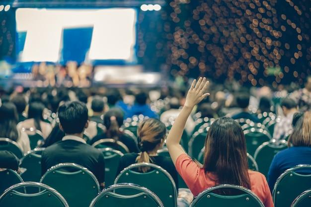 Vista posterior de la audiencia con la mano puesta para responder la pregunta del orador en el escenario.