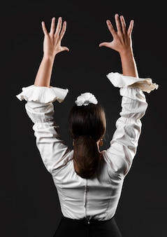 Vista posterior bailarina de flamenca con los brazos arriba
