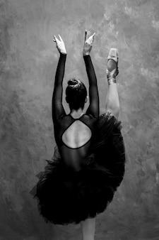 Vista posterior de la bailarina con una pierna arriba.