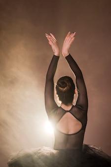 Vista posterior de la bailarina posa con humo