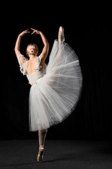 Vista posterior de la bailarina en vestido tutú con pierna arriba