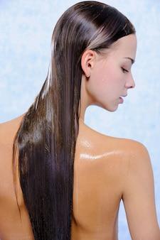 Vista posterior de bastante joven mujer con pelos largos mojados