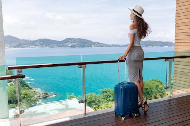 Vista posterior: una bella turista con una figura lujosa en un sombrero posa con su equipaje en el balcón, que ofrece una hermosa vista del mar y las montañas. viajes y vacaciones.