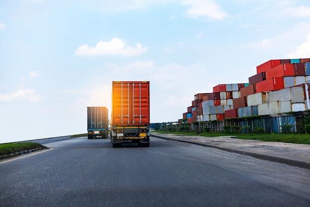 Vista posterior del camión contenedor rojo en el puerto de barcos de logística