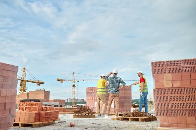 Vista posterior de un capataz de pie ante dos jóvenes constructores con chalecos de seguridad y cascos protectores en el sitio de construcción