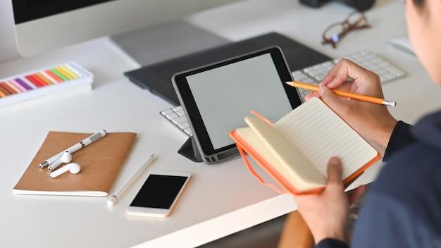 Vista posterior captura recortada del joven creativo mientras toma nota y se concentra en su tableta de pantalla en blanco en el escritorio.