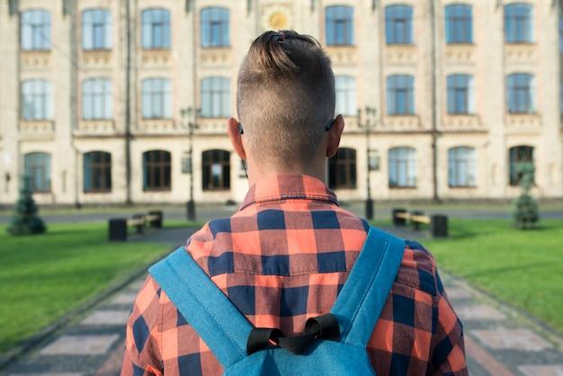 Vista posterior de cerca hasta adolescente caminando a la escuela secundaria