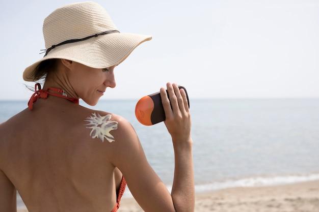 Vista posterior de cerca mujer que aplica protector solar en la espalda
