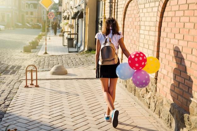 Vista posterior chica adolescente estudiante de la escuela con globos