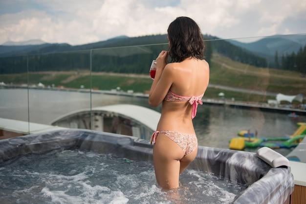 Vista posterior de la chica morena en bikini bebiendo cócteles, de pie en el jacuzzi al aire libre en vacaciones