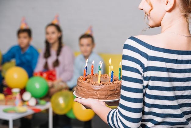 Vista posterior de la chica con pastel de cumpleaños de chocolate con velas encendidas en la fiesta