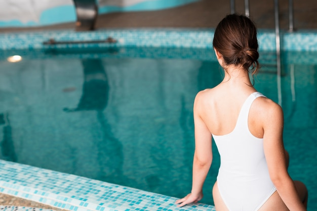 Vista posterior chica posando cerca de la piscina