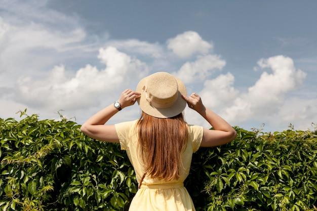 Vista posterior chica posando con planta