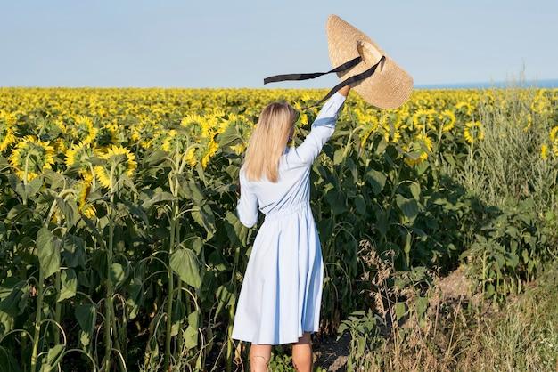Vista posterior chica sosteniendo su sombrero en un campo con flores de sol