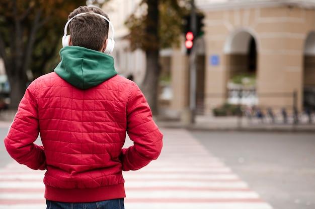 Vista posterior chico con auriculares al aire libre