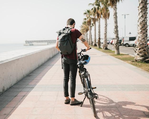 Vista posterior de un ciclista de pie junto a la bicicleta