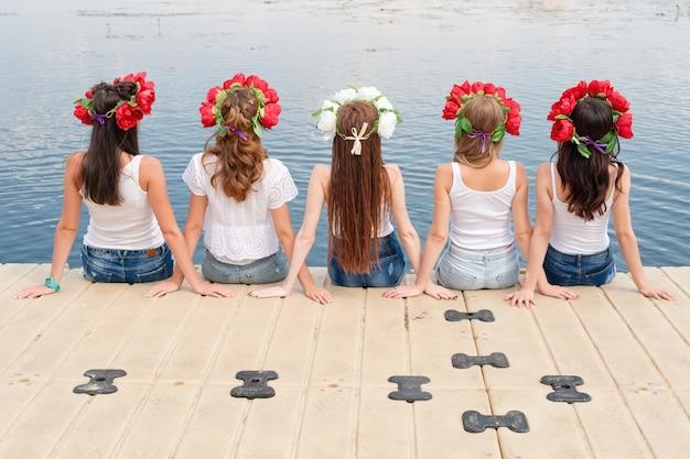 Vista posterior de cinco señoritas, con coronas de flores, jeans y camisetas blancas.