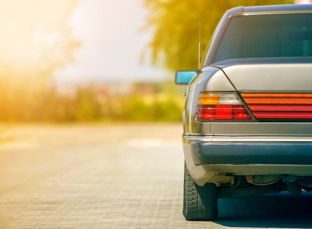 Vista posterior del coche plateado estacionado en una calle pavimentada en una zona tranquila. concepto de transporte y estacionamiento urbano.
