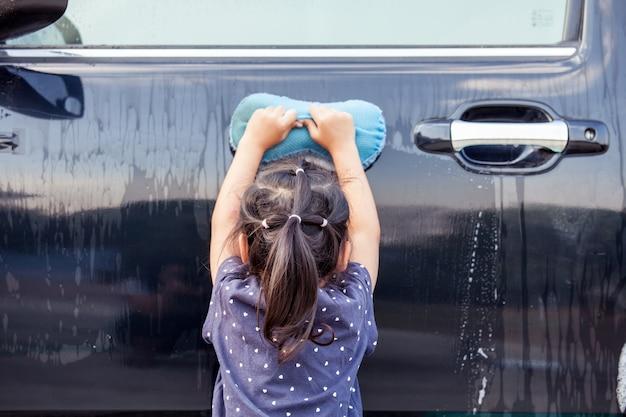 Vista posterior del coche que se lava de la niña asiática linda infantil