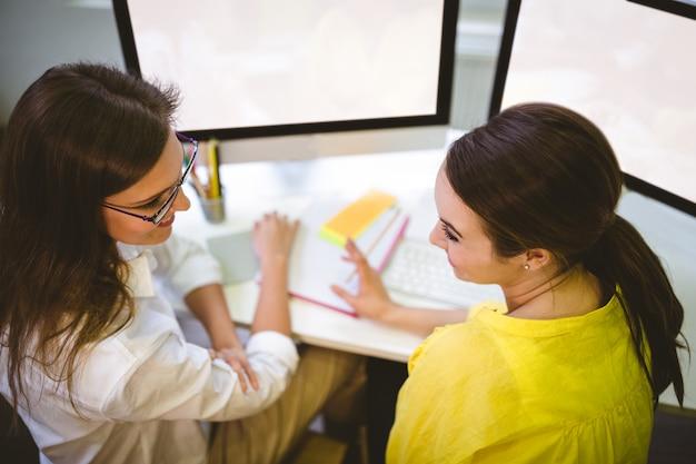 Vista posterior de colegas felices hablando en la oficina creativa