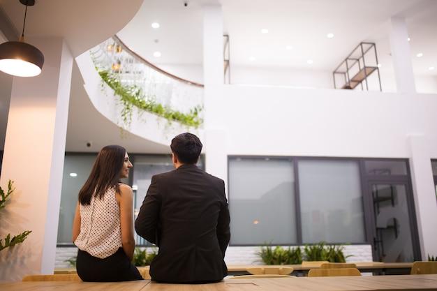 Vista posterior de colegas felices sentados en el vestíbulo durante las vacaciones