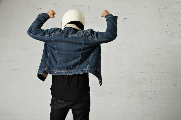 Vista posterior del cuerpo en forma del motociclista joven lleva casco, camiseta henley de manga larga negra y chaqueta de mezclilla del club con las manos en alto