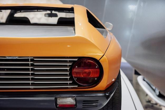 Vista posterior del cupé deportivo retro amarillo con retroiluminación trasera derecha, llantas anchas, disco cromado y espejo.