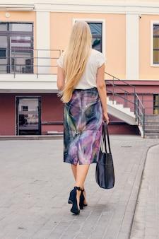 Vista posterior de una dama rubia en blusa y falda con un bolso que se acerca a la oficina