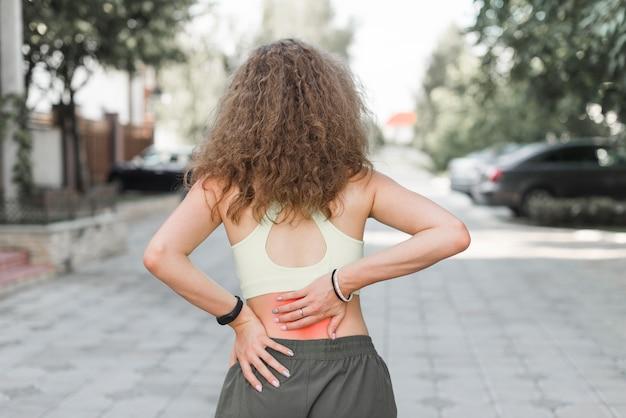 Vista posterior de la mujer de pie en la calle con dolor de espalda