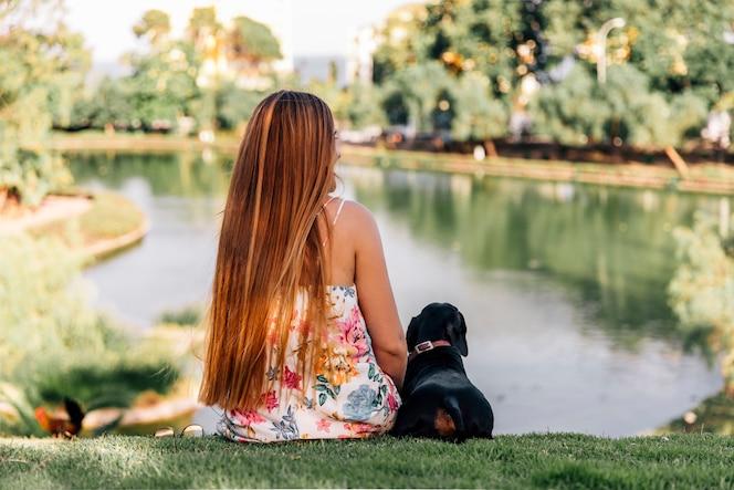 Vista posterior de la mujer y del perro salchicha que se sientan cerca del estanque