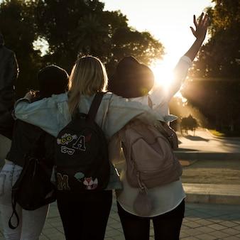 Vista posterior de mujeres caminando durante la puesta de sol