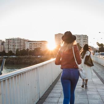 Vista posterior de mujeres caminando sobre el puente