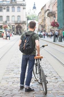 Vista posterior de un hombre con su bicicleta de pie en la calle