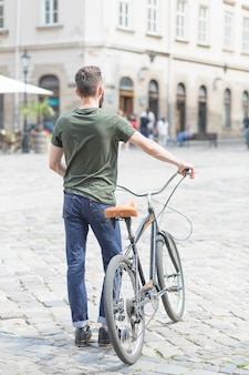 Vista posterior de un hombre de pie con su bicicleta en la ciudad