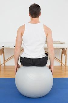 Vista posterior de un joven sentado en una pelota de yoga