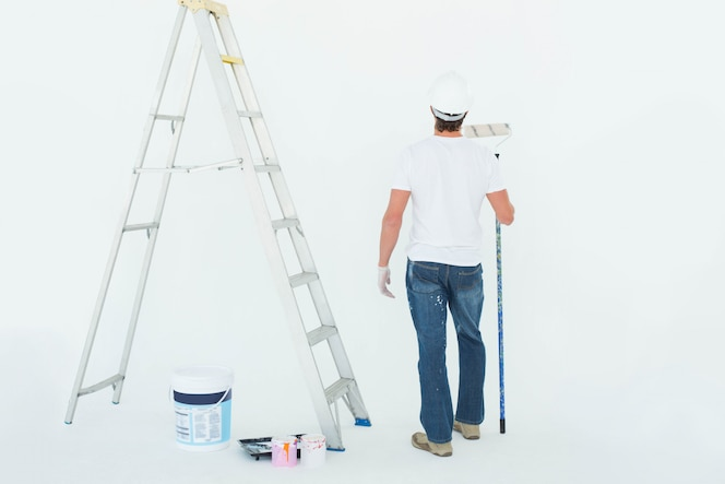 Vista posterior del hombre con rodillo de pintura por escalera sobre fondo blanco